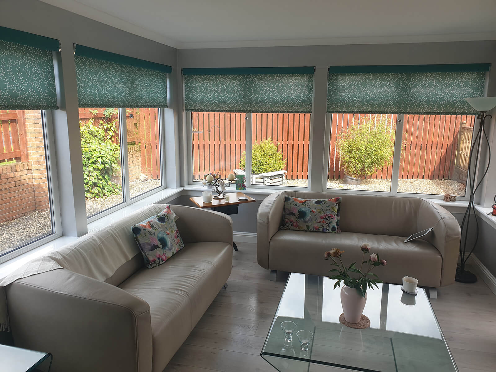 Bright room extension with lots of windows, green roller blinds, cream leather sofa and glass coffee table