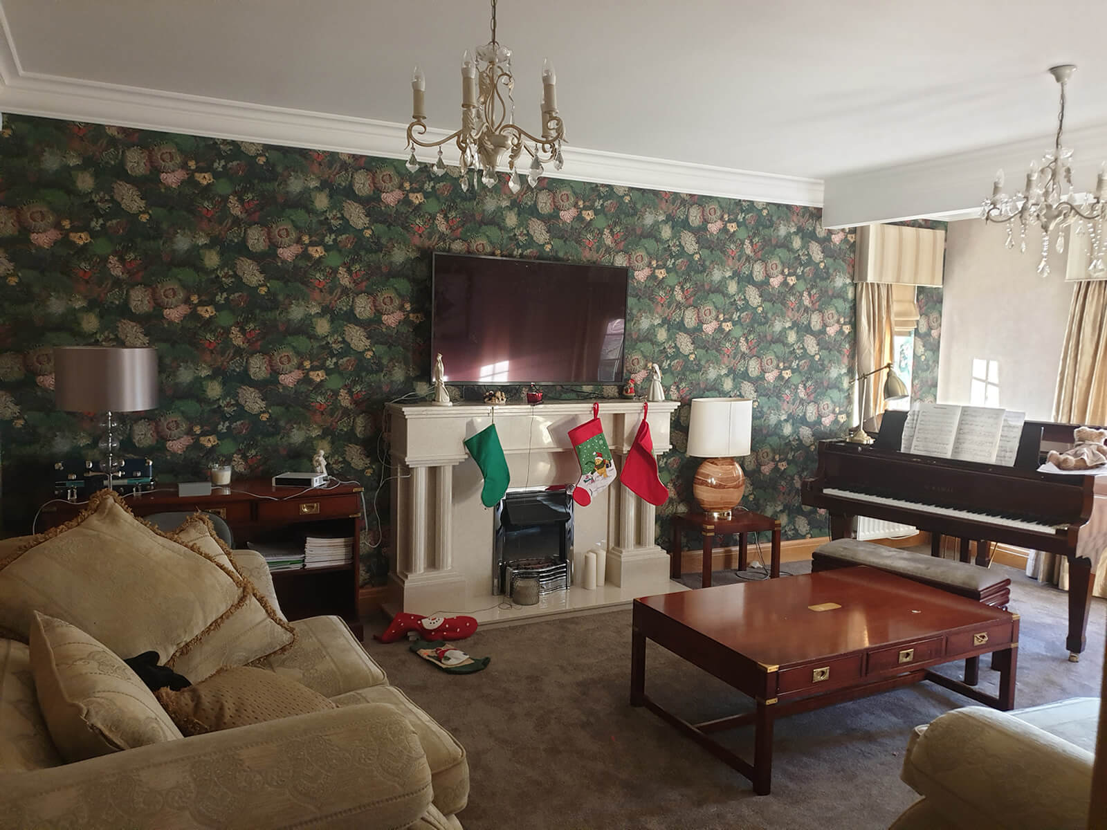 Traditional style living area with green patterned wallpaper, cream sofa, mahogany coffee table and piano