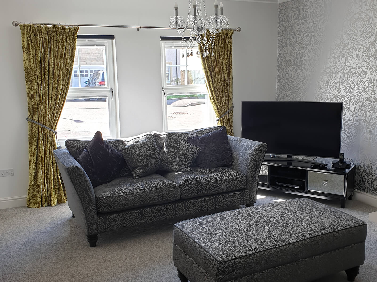 Minimalist lounge with greay sofa, silver patterned wallpaper and yellow curtains